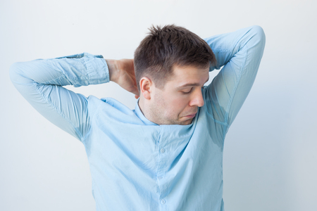 Caucasian, young man is worried and shows sweating stain problem with sweating - hyperhidrosis Stock Photo