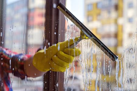 노란색 장갑에 손에 창문을 세척하는 스크레이퍼. 봄에 더럽고 먼지가 많은 창문을 닦으십시오.
