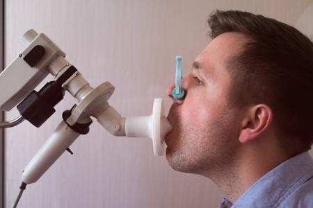 Hombre joven que prueba la función respiratoria por espirometría Foto de archivo