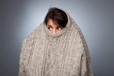A girl with a social phobia hides her face in a sweater. She looks frightened around