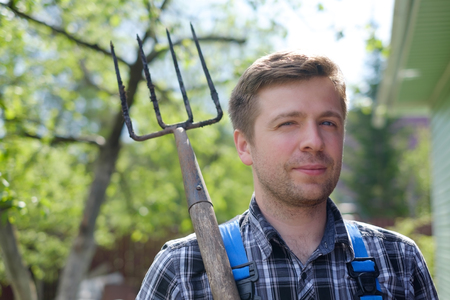 dibble: Portrait of caucasian handsome mature man standing with pitchfork on summer day Stock Photo