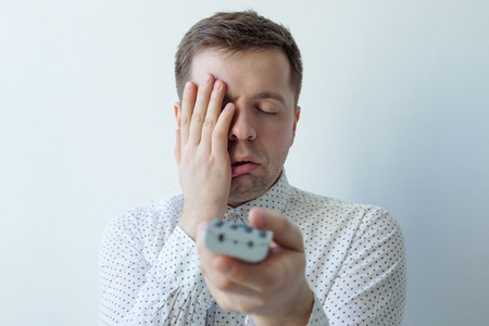 changing channel: Bored man watching tv and zapping closing face with hand Stock Photo