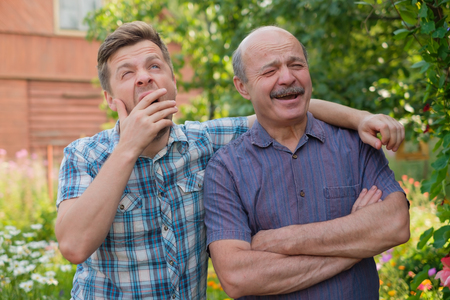 two yawning tired men at county side at sunny day Stock Photo