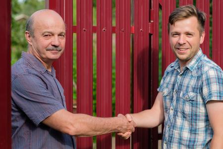 Twee boeren schudden handen en pakken elkaar aan