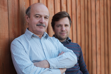 Father and son stand together near wooden background. Stock Photo