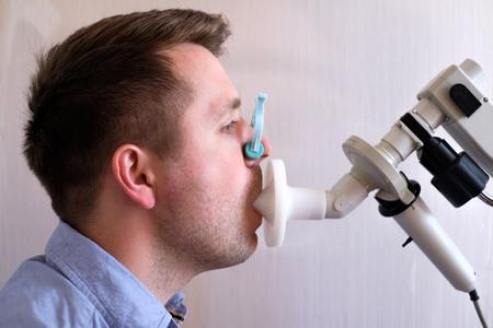 Hombre joven que prueba la función respiratoria por espirometría