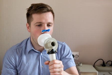 Young man testing breathing function by spirometry Foto de archivo