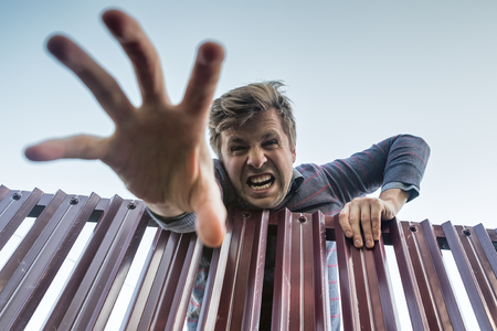 Angry man climbs furiously over the fence, breaking the boundaries of private property and pulling his hand down