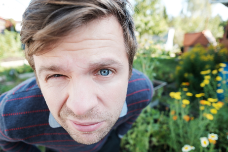 Portrait of a man with blue eyes looking at the camera with questioning and suspicious facial expression Stock Photo