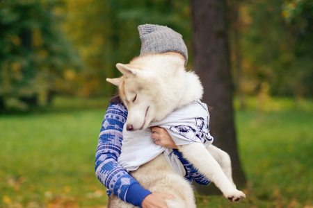 The relationship between the owner and the dog. Woman is holding the husky. Stock Photo