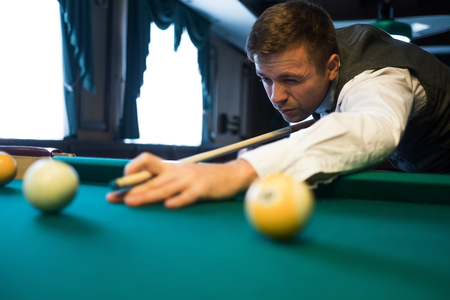 snooker halls: Young caucasian man playing billiards ready to shoot. Stock Photo