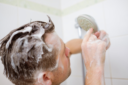 A young man with a soapy head is standing in the bathroom and looks at the shower with perplexity.