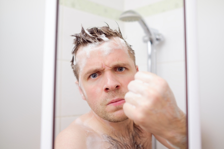 An angry man is showing a fist. He takes a shower and tries to protect his private space.