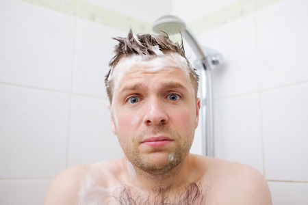 Worried caucasian foamed young man after the water in the shower was turned off, looking at the camera.