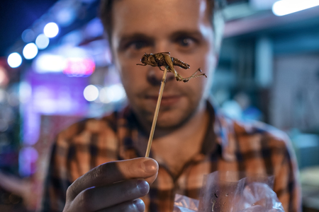 Caucasian young male eating cricket at night market in Thailand. Archivio Fotografico
