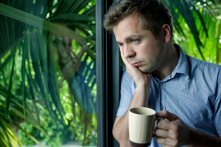 Close up portrait of businessman drinking coffee. man looking trough window and holding cup