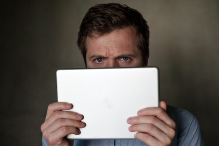 Serious mature middle aged man looking into tablet and frown his face.
