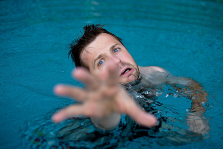 Drowning caucasian man in swimming pool asking for help. He stretching his hands in fear.