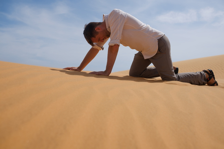 Man walking alone in the sunny desert. He is lost and out of breath. No water and energy.