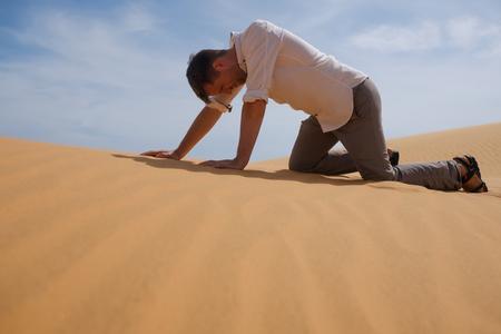 Hombre caminando solo en el desierto soleado. Él está perdido y sin aliento. Sin agua y energía. Foto de archivo