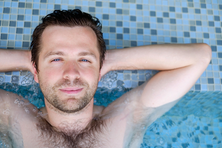 Content caucasian man in a swimming pool.
