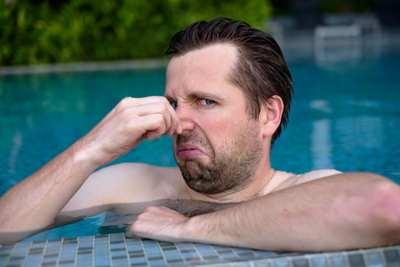 Young man with disgust on his face pinches nose, something stinks, very bad smell in swimming pool because of chloride. Stock Photo