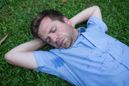 Caucasian, young man is resting on green grass and looking on his wet shirt. Stock Photo