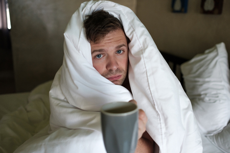 Caucasian male with lack of sleep because he has flu stting in bed and ask for water or medicine