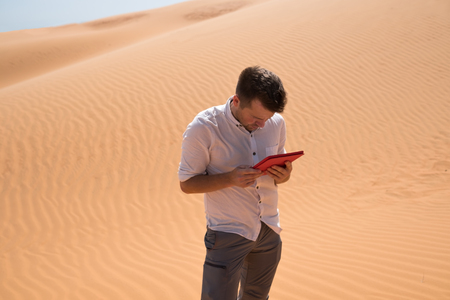 Lost in the desert. Caucasian man sitting on sand with tablet. He is lost and looking in map where to go
