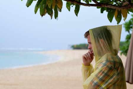 Man in a yellow raincoat on tropical seashore during rain.
