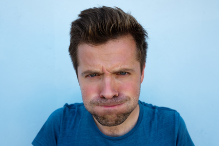 Humorous emotional portrait of grimacing young man