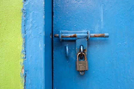 Old lock on the door but the door is opened. Green and blue wall.