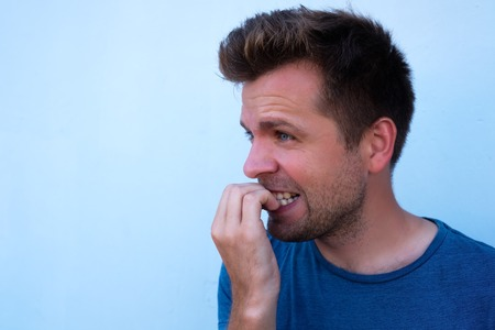 Caucasian mature man gnawing nails. Bad habit when you fell nervous and worry a lot. Stock Photo