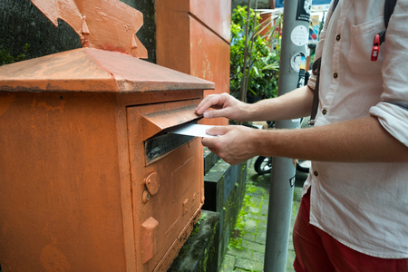 Closeup on a male hand putting a letter in a red letterbox. Concept of vintage type of communication.