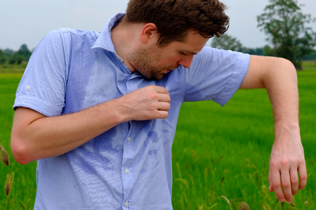 Man with hyperhidrosis sweating very badly under armpit in blue shirt, isolated on grey Фото со стока