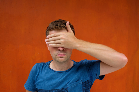 Caucasian man closes eyes with her hands. He does not want to see something and to be a witness. Stock Photo