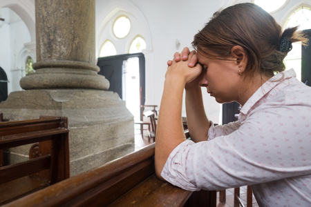 Praying woman in christian church praying God for help Banque d'images
