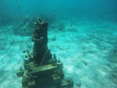 Kamienny posąg stojący na piaszczystym dnie morza. Zdjęcie Seryjne