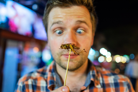 Caucasian young male eating cricket at night market in Thailand. Stockfoto