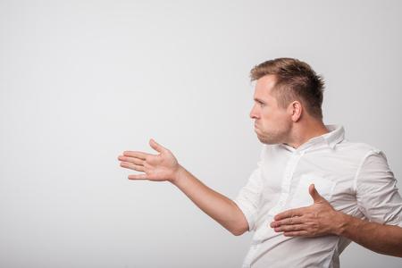 Caucasian man in white t-shirt showing something in very strange manner.