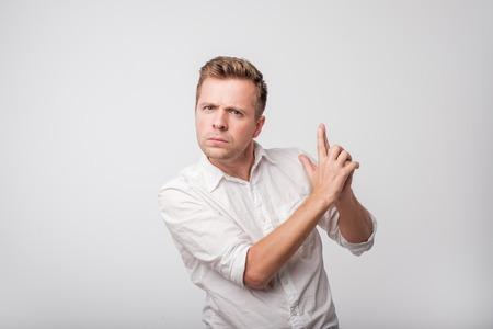 Caucasian man in white shirt pretending he has a dun in hands. Stock Photo