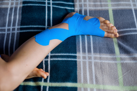Elastic therapeutic blue tape applied to patients left leg.