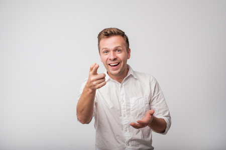Young european man, laughing, pointing with finger at someone, something, isolated on white background. Stock Photo