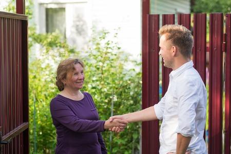 Die Nachbarn besprechen die Neuigkeiten und stehen am Zaun. Eine ältere Frau, die mit einem jungen Mann spricht