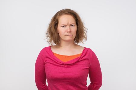 Joven mujer europea divertida se siente ofendida. Ella mira con incredulidad a la cámara
