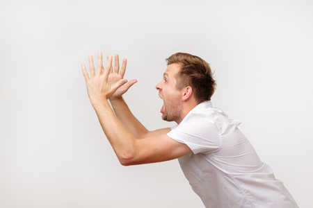 Side view photo of young european man in white t-shirt shouting and shaking his hands. Stock Photo