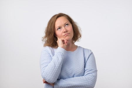 Middle aged european woman thinking and looking up, confused about an ide