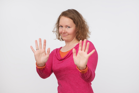 European woman saying thanks but no, denying proposal, making stop gesture with her hands, looking at camera. It is enough concept