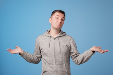 Studio portrait of confused handsome guy showing I have no idea gesture. European man shrugging shoulders and raising hands, standing against blue background. I did not know it was yours
