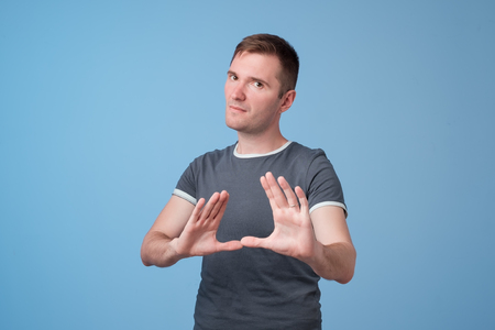 Portrait of european serious young man stretching hand towards camera with stop or hold gesture, standing against blue background. Stay away from me. I do not agree with you concept